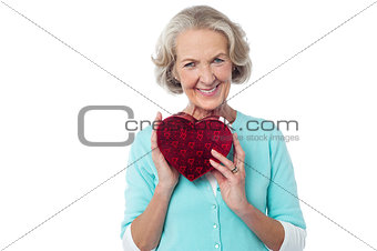 Aged woman symbolizing love, holding gift.