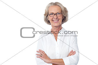 Portrait of smiling old lady, arms crossed.
