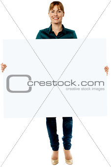 Attractive woman holding blank ad board