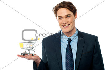 Businessman presenting shopping cart