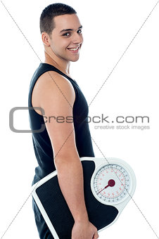 Fitness man with weighing scale