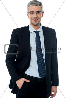 Business man smiling, hand in pocket