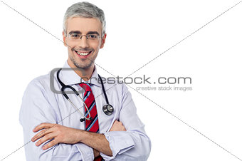 Smiling aged physician, arms crossed