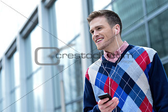 Casual man hearing music outside modern building