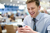Happy young executive sitting with smartphone