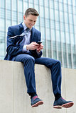 Smiling businessman using his smartphone
