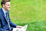 Businessman reading newspapers in park