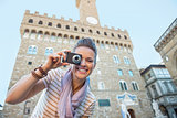 Happy young woman taking photo in front of palazzo vecchio in fl