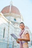 Portrait of happy young woman with map near cattedrale di santa