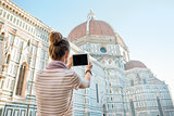 Young woman taking photo with tablet pc of cattedrale di santa m