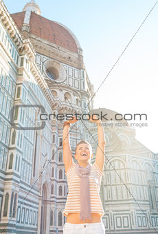 Portrait of happy young woman rejoicing in front of cattedrale d