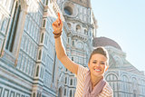 Happy young woman pointing in front of cattedrale di santa maria