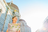 Happy young woman with map in front of cattedrale di santa maria