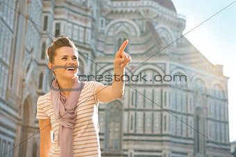 Portrait of happy young woman pointing on copy space in front of