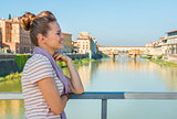 Thoughtful young woman standing on bridge overlooking ponte vecc