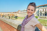 Happy young woman standing on embankment overlooking ponte vecch