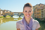 Portrait of happy young woman standing on bridge overlooking pon