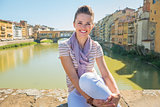 Portrait of happy young woman sitting on bridge overlooking pont