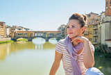 Young woman sitting on bridge overlooking ponte vecchio in flore