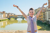 Happy young woman standing on bridge overlooking ponte vecchio i