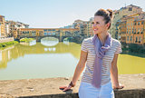 Happy young woman sitting on bridge overlooking ponte vecchio in