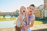 Portrait of smiling mother and baby girl standing on bridge over