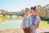 Happy mother and baby girl hugging on bridge overlooking ponte v