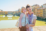 Portrait of happy mother and baby girl standing on bridge overlo