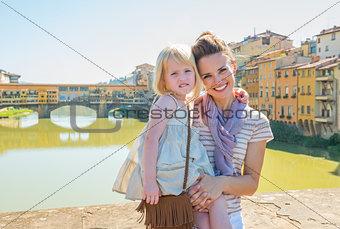 Portrait of happy mother and baby girl standing on bridge overlo