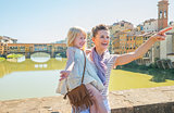Happy mother and baby girl standing on bridge overlooking ponte