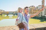 Happy mother and baby girl standing on bridge overlooking ponte