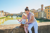 Mother and baby girl sitting on bridge overlooking ponte vecchio