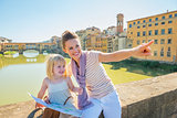 Happy mother and baby girl with map sitting on bridge overlookin