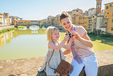 Happy mother and baby girl checking photos in camera on bridge o