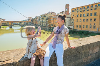 Baby girl taking photo of mother while sitting on bridge overloo