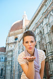 Portrait of happy young woman blowing kiss in front of cattedral