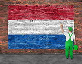 House painter paints flag of Hetherlands on brick wall