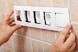 Hands installing decorative frame on electrical sockets