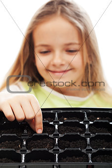 Little girl planting putting seeds into germination tray