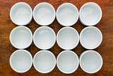 dozen of empty white tasting bowls
