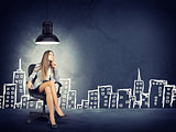 Woman wearing jacket, blouse sitting with legs crossed. Background sketch of buildings