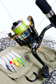 Fishing rod and lures on white.