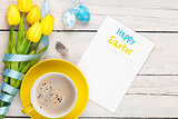 Easter greeting card with blue and white eggs, yellow tulips and