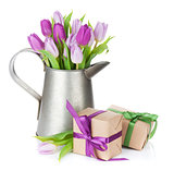 Purple tulip bouquet in watering can and gift boxes
