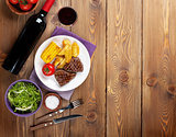 Steak with grilled potato, corn, salad and red wine