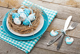 Easter eggs nest on plate with silverware