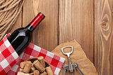 Red wine bottle, corks and corkscrew over wooden table backgroun