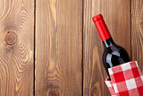 Red wine bottle with towel on wooden table