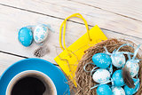 Easter background with blue and white eggs in nest, yellow tulip