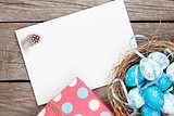 Easter greeting card with blue and white eggs and gift box over